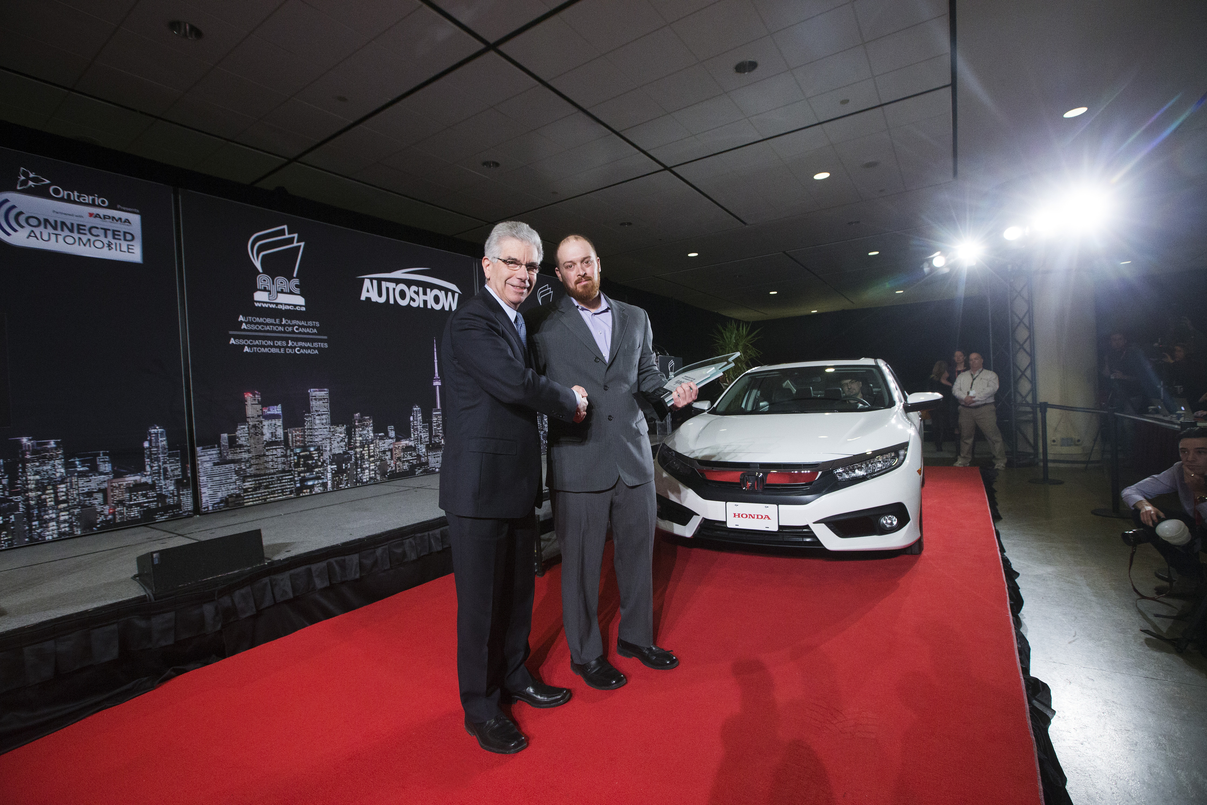 Honda President and CEO Jerry Chenkin, left, and Justin Pritchard, CCOTY co-chair, right, pose for a photo with the Honda Civic which claimed top honours as the 2016 Canadian Car of the Year (CCOTY).   (Photos By: Michelle Siu)