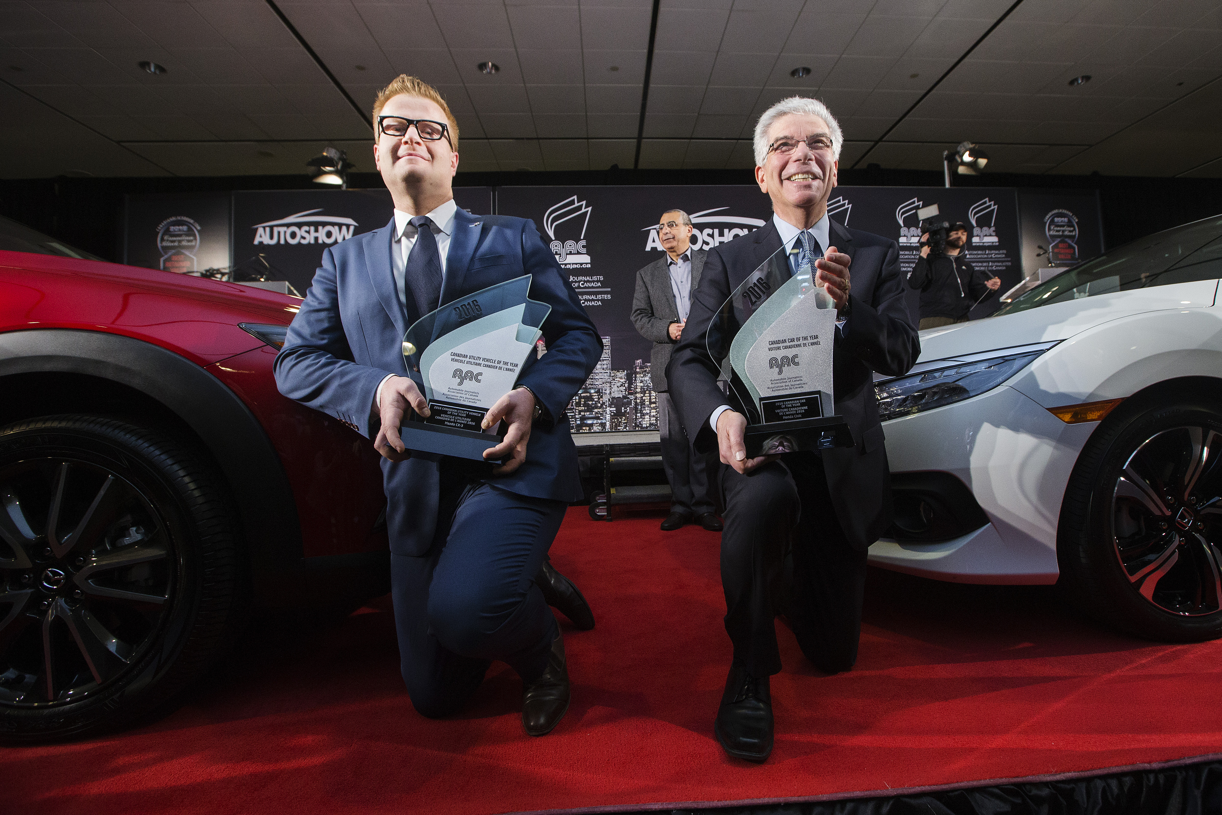 Vincent Reboul, Marketing Director at Mazda Canada Inc.left, poses for a photo with the Mazda CX-3 which was declared the 2016 Canadian Utility of the Year and Honda President and CEO Jerry Chenkin, right, which was declared the 2016 Canadian Car of the Year (CCOTY).  (Photos By: Michelle Siu)