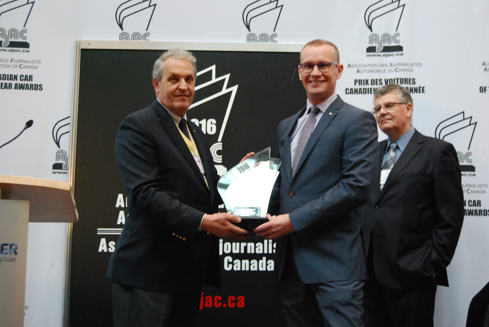 Accepting the award is Scot Rasmussen, Regional Manager, Western Region, Mazda Canada. Presenting is Kevin Corrigan, background is Bob McHugh.